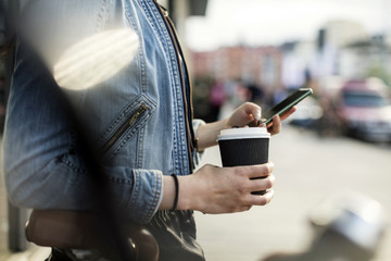 Midsection of a woman holding a smart phone and coffee cup in city