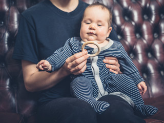Mother offering baby teething ring