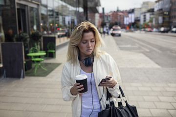 Woman with smartphone  and coffee in street