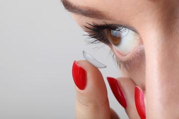 Junge schöne Frau setzt eine Kontaktlinse ein