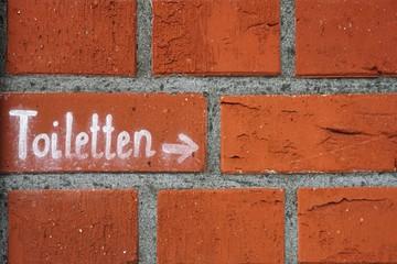 Schriftzug mit dem Hinweis auf Toiletten an einer Hauswand