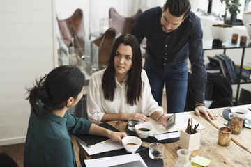 High angle view of business people talking while having coffee at table in meeting