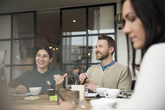 Happy business people talking while having coffee at table during meeting in office
