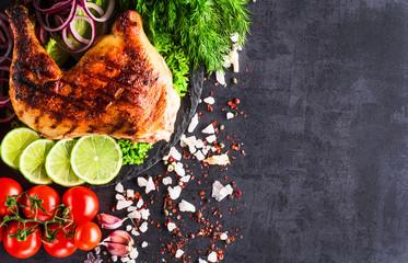 Roasted chicken legs with vegetables on dark background