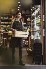 Woman holding vegetables crate while walking in store