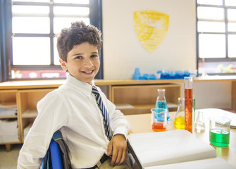 School boy (10-11) in science class, with lab notebook