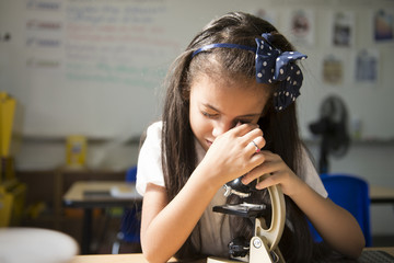 Girl using microscope in classroom