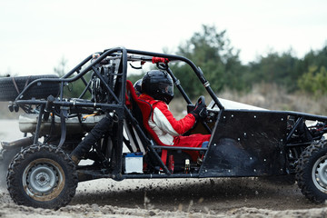Sports car racing on the track. The driver behind the wheel of a buggy with a second driver