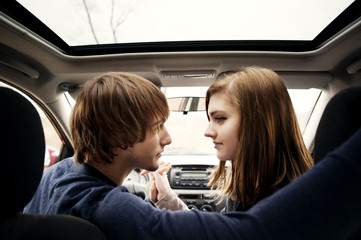Teenage girl (16-17) looking at her boyfriend in car