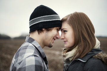 Teenage girl (16-17) face to face with her boyfriend in field