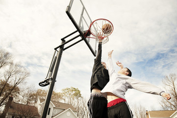 Teens (14-15 ) playing basketball in suburbs