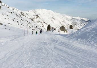 Skiers on a piste in alpine ski resort