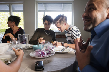 Friends using phone while family talking at dining table in dinner party