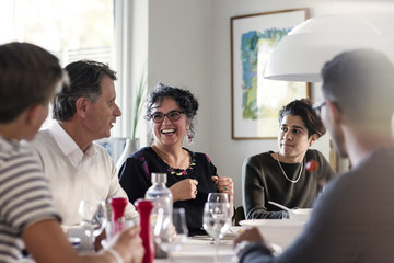 Happy friends discussing at dining table in dinner party