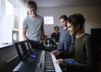 Siblings looking at young man playing piano keyboard in brightly lit room