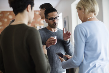 Man with glass gesturing while talking to woman holding phone at social gathering