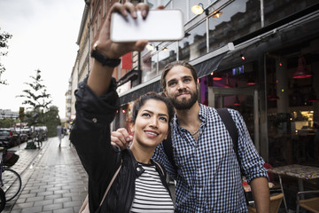 Couple taking selfie through smart phone while standing by sidewalk cafe in city