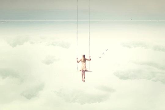 upside down surrealistic minimal woman swings in the air