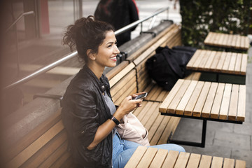 Smiling woman holding mobile phone while sitting on wooden bench at sidewalk cafe