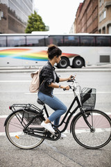 Side view of woman using mobile phone while riding bicycle on city street