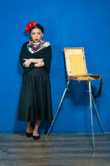 Beautiful girl in spanish clothing with easel