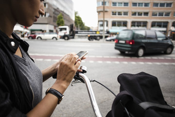 Cropped image of woman with bicycle using mobile phone while standing by street in city