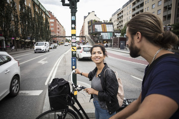 Smiling woman with bicycle looking at friend while standing amidst city street