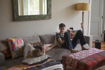 Boy (12-13) and teenage girl (16-17) relaxing on sofa