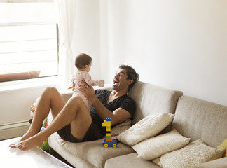 View of father playing with daughter (2-5 months)