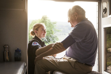 Paramedic examining senior patient in ambulance