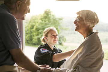 Paramedic taking care of senior patient sitting in ambulance