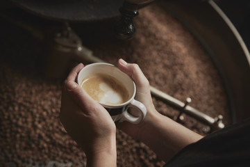 A coffee shop. A person holding a fresh brewed cup above a metal drum with roasting coffee beans.