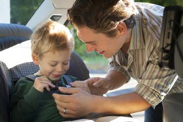 Dad buckling son (2-3) in car seat