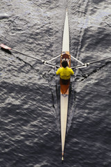 A man sculling in a single scull rowing boat, on the water.  Overhead view.