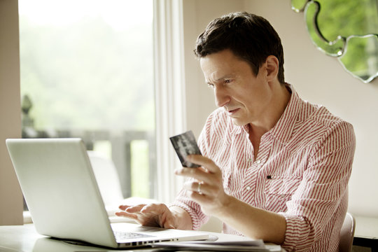 Mature man paying with credit card on computer