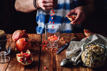 Man Puts Pomegranate Seeds into the Glass.