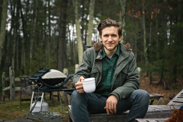 Man in woods drinking coffee