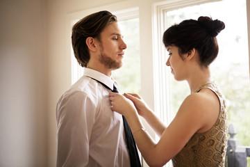 Girlfriend fixing boyfriends tie