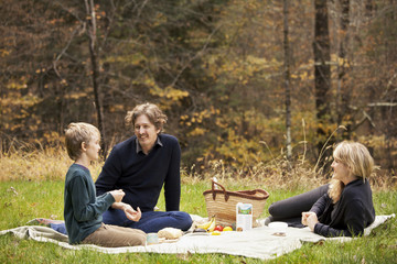Parents and son ( 8-9 ) having picnic in forest