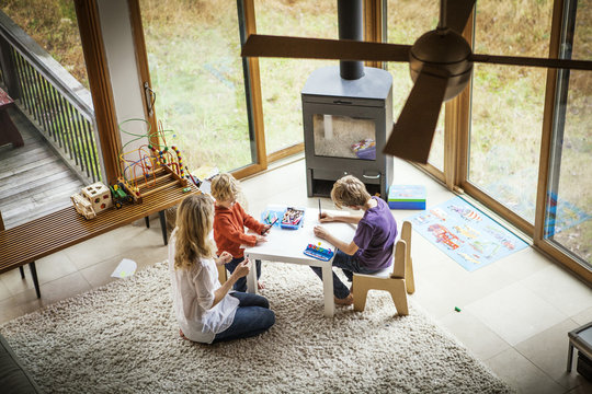 Mother with sons (18-23 months, 8-9) drawing in living room