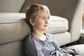 Portrait of boy ( 8-9 ) sitting in front of sofa