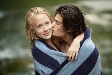 Couple kissing in towel by stream
