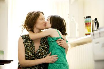 Mother hugging daughter (8-9) in kitchen