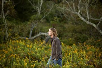 Young man walking through meadow