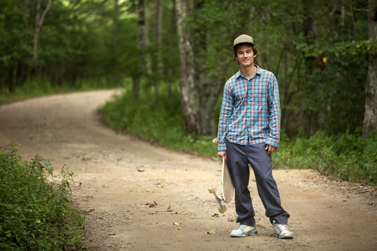 Portrait of smiling man with skateboard