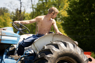 Shirtless farmer on tractor