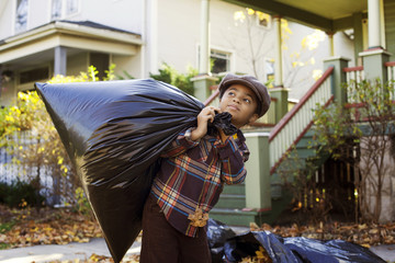 Boy (8-9) carrying bag of autumn leaves
