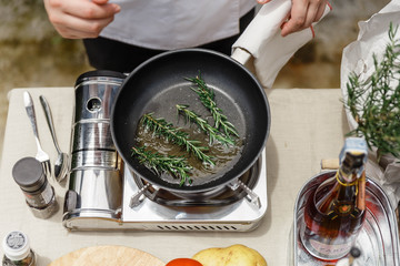 Chef Fried Rosemary Leaves in Olive Oil in a Pan for Making Rosemary Oil.