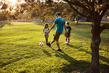 Father and children (4-5, 6-7) playing football