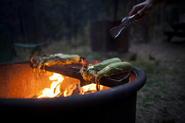 Close-up of man's hand cooking corn on barbecue grill
